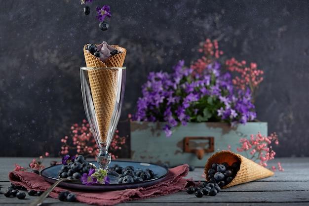 紫色の花と果実に囲まれたワッフルカップのブルーベリー果実。夏のテーマ浮上 Premium写真