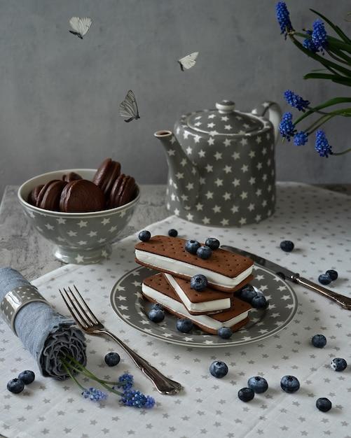 チョコレートビスケットクッキーと蝶とサンドイッチのアイスクリーム。折り畳まれたアイスクリームのスタック Premium写真