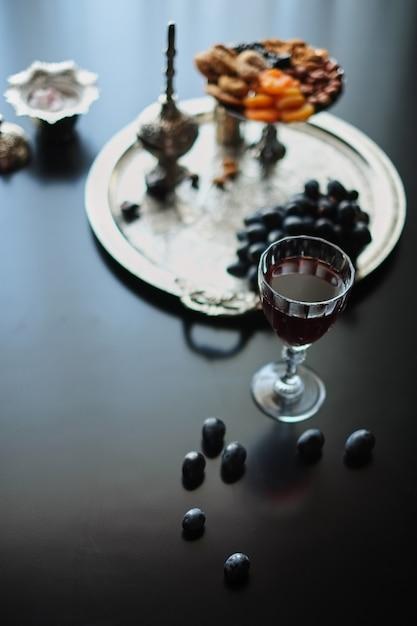 Натюрморт с бокалом вина и сухофруктами на черном фоне Premium Фотографии