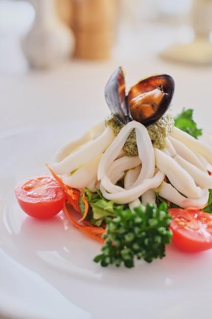 イカとムール貝の白い背景の上の白い皿の上の野菜 Premium写真