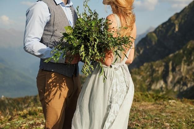 花嫁は彼女の目を閉じて彼女の婚約者、山の背景に何かをささやきます Premium写真