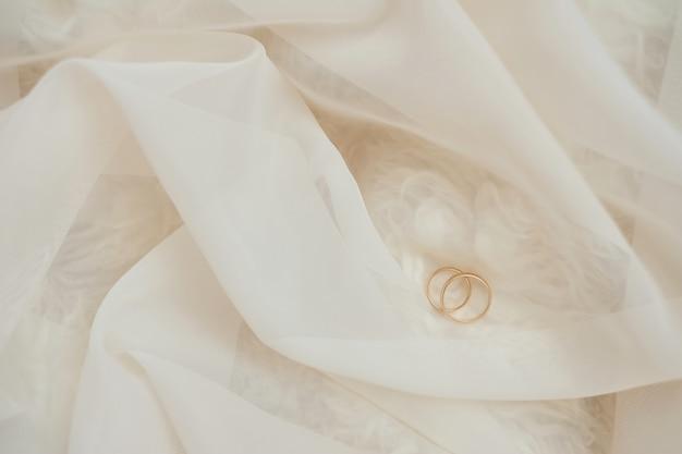 パステルカラーのレースの黄金の結婚指輪。浅いフォーカス明るい背景 Premium写真