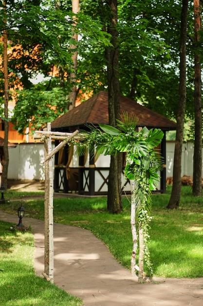 Свадебная арка украшена зелеными листьями на открытом воздухе свадебная церемония Premium Фотографии