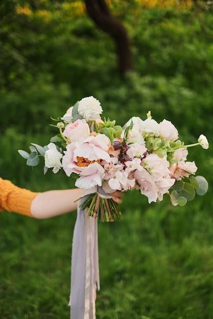 花嫁、デビッドオースティンローズ、緑の背景の手の中のウェディングブーケ Premium写真