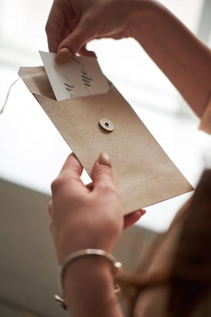 Надписи черном, девушка держит открытку