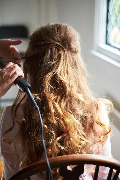 電気ヘアカーラーと花嫁の結婚式のヘアスタイルを閉じる Premium写真