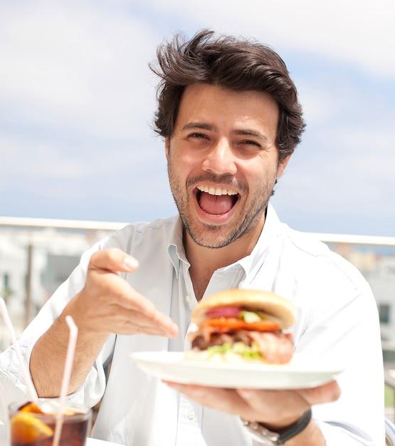 ハンバーガーを食べる若い男 Premium写真