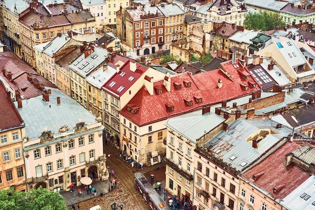 古いリヴィウの眺め。歴史的な市内中心部の家の明るい色の屋根 Premium写真