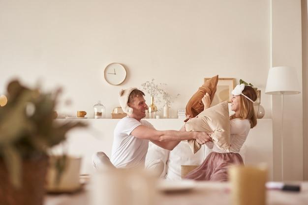 笑ってベッドで遊んで愛のペア。男と女は枕を戦う。若い幸せなカップルが自宅の寝室のベッドの枕を打つ Premium写真