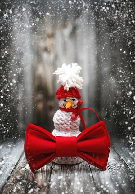 黒い木製の表面に雪で新年冬雪だるまの装飾。コピースペースで休日新年ポストカードフレームデザイン Premium写真