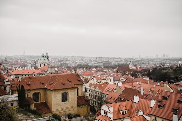 赤い屋根と霧の中で教会とプラハの街。プラハ旧市街の街の眺め。素朴なグレーの色調 Premium写真
