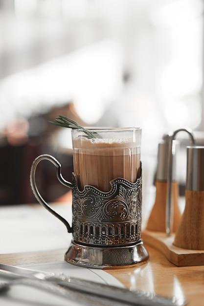 ビンテージメタルカップホルダーにローズマリーの枝が付いている熱いココアのマグカップ。 Premium写真