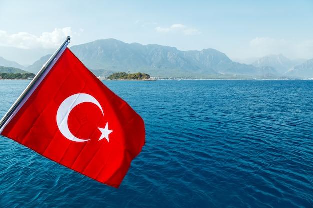 海と海岸を背景に風になびいてトルコ国旗 Premium写真