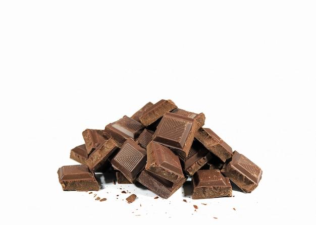 Куча темных кусочков шоколада, изолированных на белом фоне Premium Фотографии
