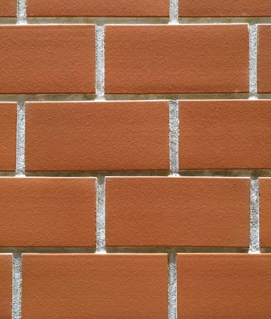 オレンジ色のテラコッタ色のレンガの壁の背景、テクスチャのクローズアップ Premium写真