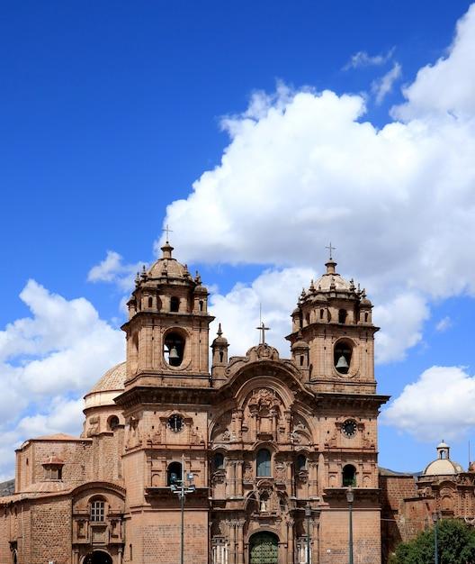 南アメリカ、ペルー、クスコの日当たりの良い鮮やかな青い空を背景にイエス・キリスト教会の教会 Premium写真