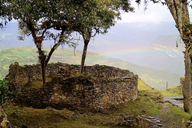 Деревья, растущие внутри округлых руин дома цитадели на вершине горы куэлап с радугой, перу Premium Фотографии
