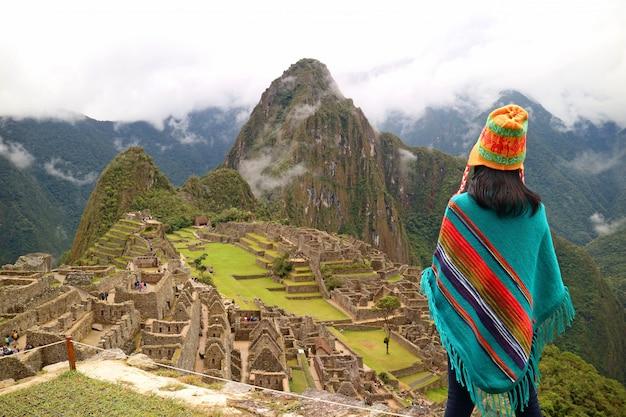 Женщина турист, глядя на знаменитые руины древних инков мачу-пикчу, регион куско, перу Premium Фотографии