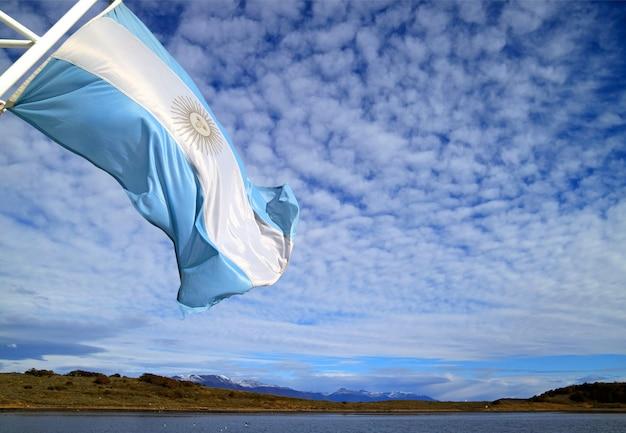 明るい曇り空を背景に日光を振るクルーズ船のアルゼンチンの旗 Premium写真