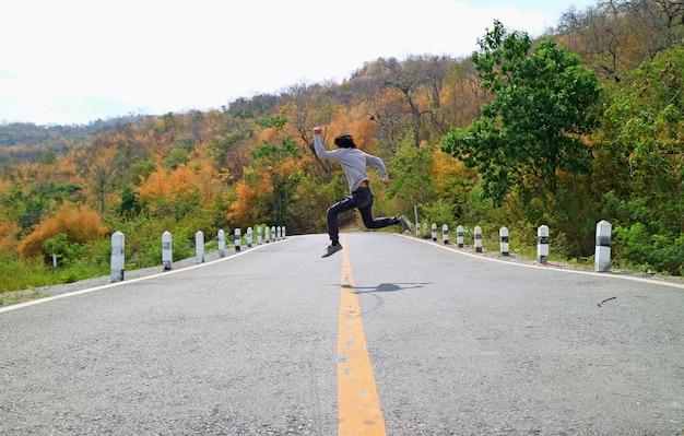 色が変わる森の中で山の道を横切ってジャンプのポーズの男 Premium写真