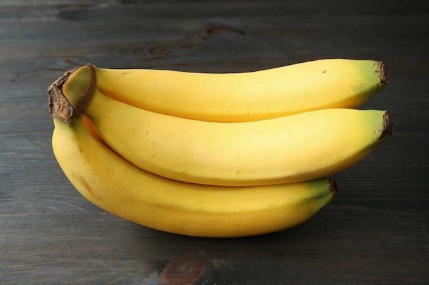 Гроздь бананов, изолированные на темные деревянные Premium Фотографии