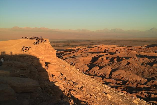 アタカマ砂漠のムーンバレーで美しい夕日を待っている多くの人々、 Premium写真