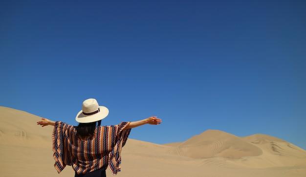 Одна женщина наслаждается потрясающим видом на пустыню уакачина в регионе ика в перу Premium Фотографии