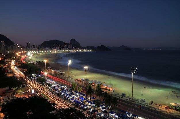 夜、リオデジャネイロ、ブラジルの距離でコパカバーナビーチとシュガーローフ山の美しい空撮 Premium写真