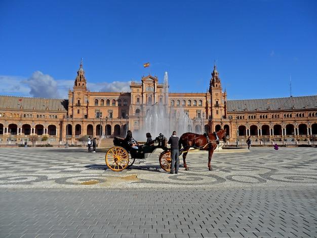 スペイン、セビリアのスペイン広場のビセンテトラバー噴水の前で馬車 Premium写真