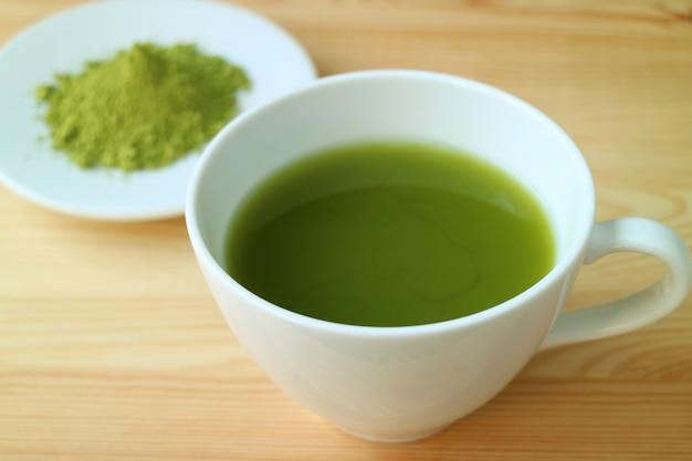 バックグラウンドで抹茶茶粉のぼやけたプレートと木製のテーブルで提供しています熱い抹茶緑茶のカップ Premium写真