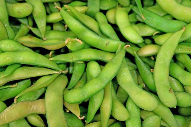 市場で販売されている新鮮な大豆または枝豆のヒープの平面図 Premium写真