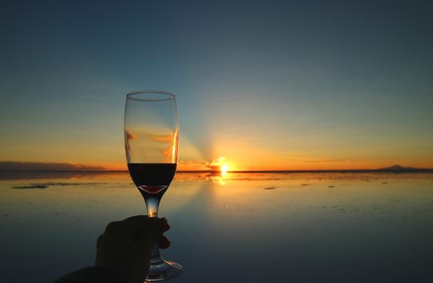 ウユニ塩原、ボリビア、南アメリカの鏡のような夕焼けへの歓声 Premium写真