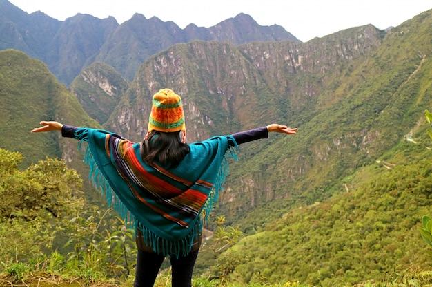 ペルー、クスコ地方、マチュピチュ、ワイナピチュ山の視点で彼女の腕を上げる女性 Premium写真