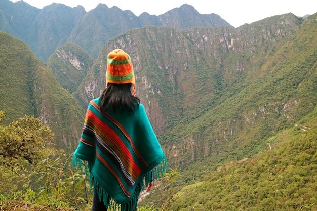 Молодая женщина, глядя на горный хребет с горы хуайна-пикчу, мачу-пикчу, перу Premium Фотографии