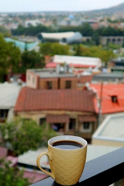 背景のぼやけた街の景色とバルコニーでホットコーヒーのカップのクローズアップ Premium写真