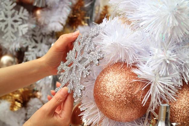 キラキラスノーフレーク形の飾りでクリスマスツリーを飾る女性の手 Premium写真