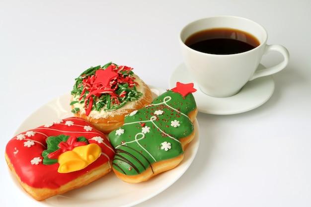 一杯のコーヒーと白いプレートにクリスマスのお菓子のプレート Premium写真
