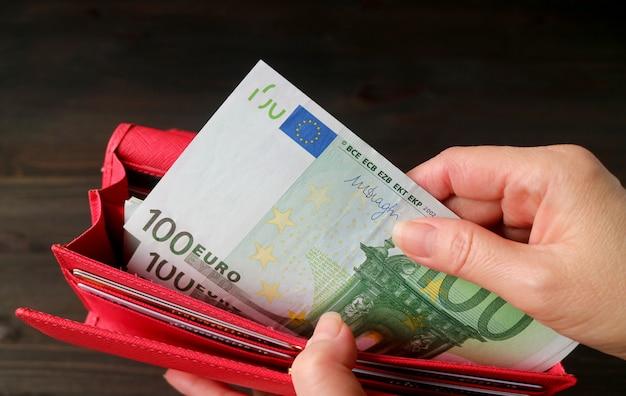Женская рука берет банкноты евро из красного кошелька Premium Фотографии
