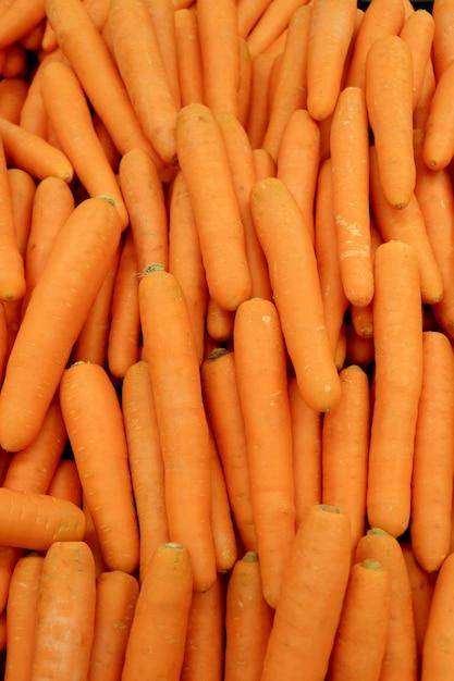 Вертикальное изображение кучи яркого оранжевого цвета свежей моркови для фона Premium Фотографии