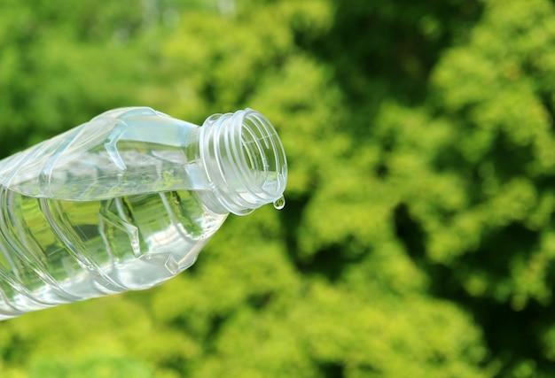 Минеральная вода крупного плана падая от пластичной бутылки с зеленой листвой Premium Фотографии
