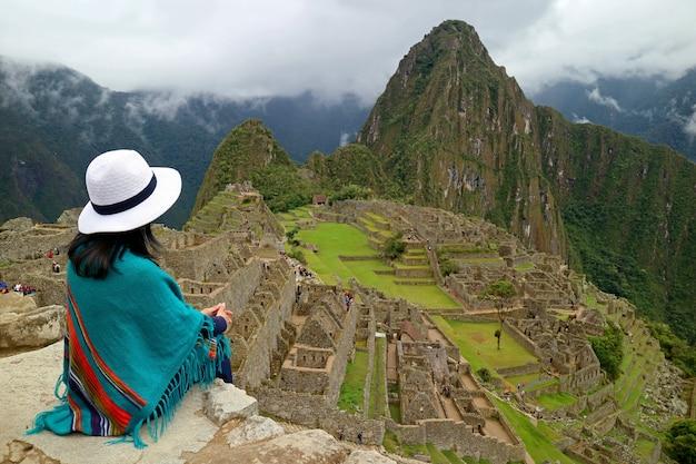 マチュピチュ、ペルーのインカ遺跡を見て崖の上に座っている女性旅行者 Premium写真