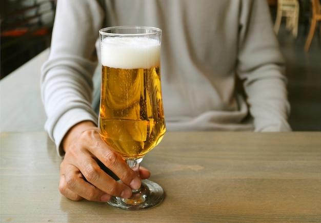 木製のテーブルにラガービールのグラスを抱きかかえた Premium写真