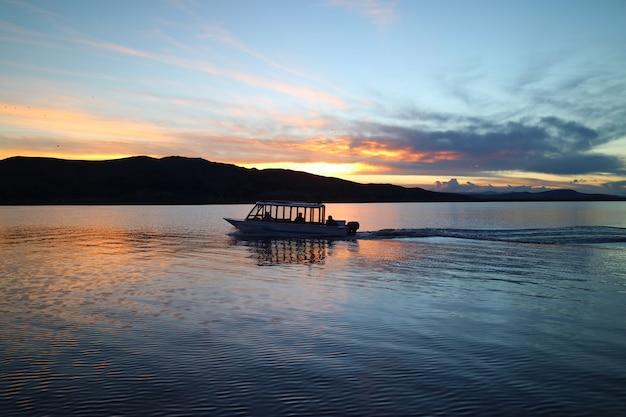 日没、プーノ、ペルーでチチカカ湖のクルージングボートのシルエット Premium写真