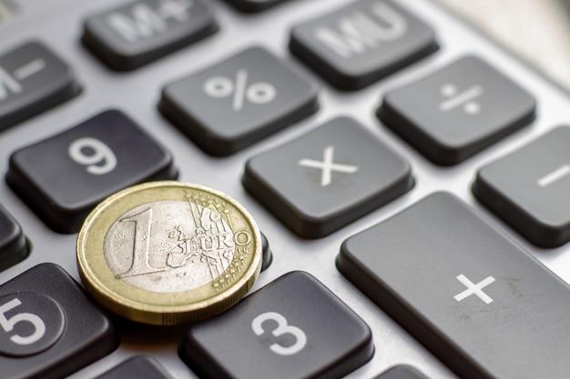 Крупный план калькулятора клавиатуры с одной монеткой евро. бизнес-концепция повышения финансов ипотечного кредита залог ставки по кредиту. Premium Фотографии