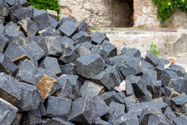 建材の石の山。石積み舗装および歩道用の石。花崗岩の暗い石畳を作ります。 Premium写真