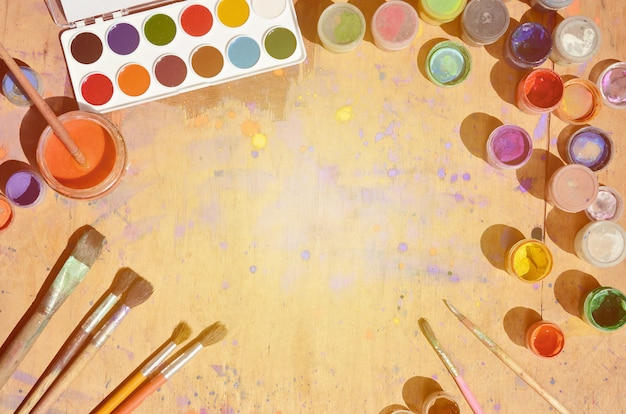 多くのブラシと水彩画とガッシュ塗料の瓶のある静物 Premium写真