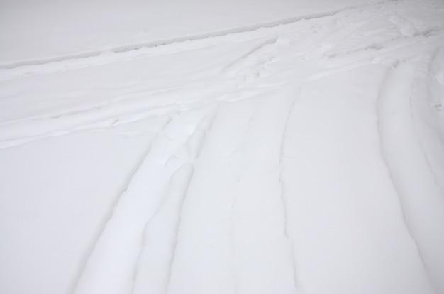 雪に覆われた道路上の車の車輪からの痕跡。 Premium写真