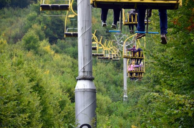 人々はケーブルカーに乗る。乗客の足は山の森に掛かる Premium写真
