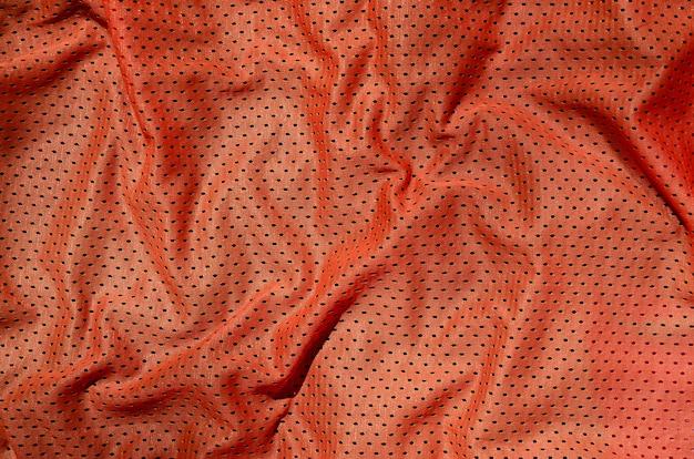 スポーツ服生地のテクスチャ背景。赤いポリエステルの平面図 Premium写真