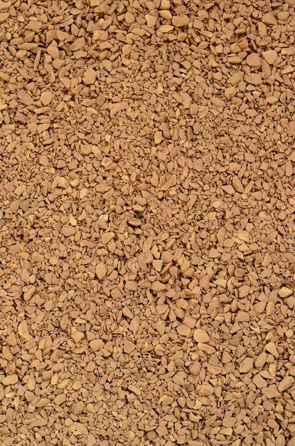 ダークブラウン色の多くの小さな小石の形で挽いたコーヒーの質感 Premium写真